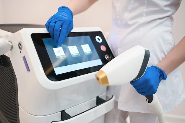 Gerät zur laser-haarentfernung und die hände einer kosmetikerin kosmetikerin in medizinischen handschuhen. epilation und spa-konzept