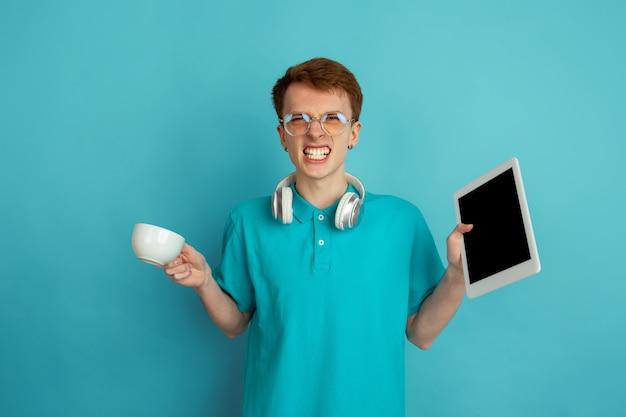 Geräte benutzen, kaffee trinken. das moderne porträt des kaukasischen jungen mannes lokalisiert auf blauer wand, monochrom. schönes modell. konzept der menschlichen emotionen, gesichtsausdruck, verkauf, anzeige, trendy.