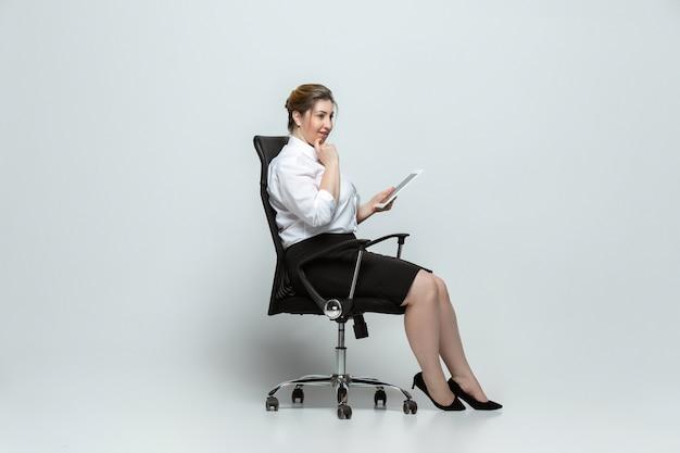 Geräte. junge frau in bürokleidung. körperpositiver weiblicher charakter, feminismus, sich selbst liebend, schönheitskonzept. plus-size-geschäftsfrau auf grauer wand. chef, schön. inklusion, vielfalt.