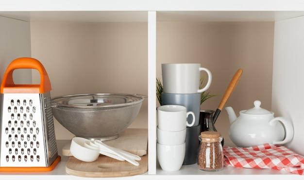 Geräte und becher, küchengeschirr auf hölzernen regalen