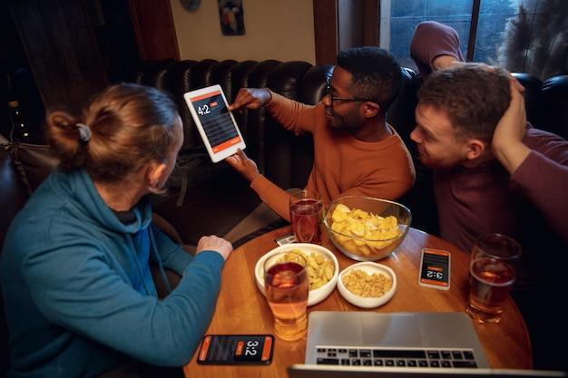 Gerätebildschirm mit mobiler app für wetten und punkte. gerät mit spielergebnissen auf dem bildschirm, begeisterte fans im hintergrund während des spiels.