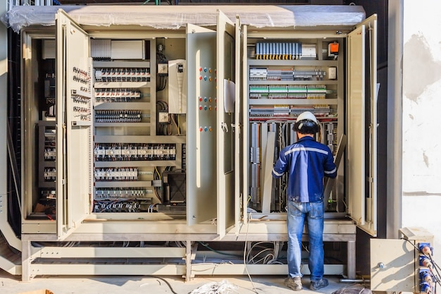 Gerätetechniker bei der arbeit verdrahtung am sps-schrank prüfen