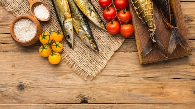 Geräucherte fische und tomaten liegen flach