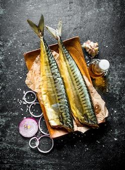 Geräucherte fischmakrele auf einem teller mit zwiebelringen und knoblauch. auf dunklem rustikalem hintergrund
