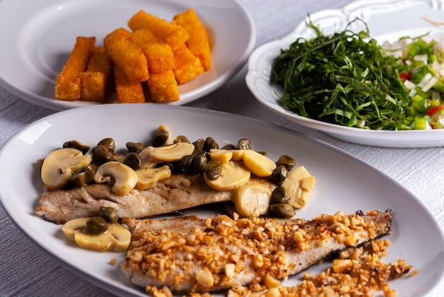Geräucherte forelle mit kapern und champignons und geräucherte forelle mit mandeln und salat und gebratener polenta