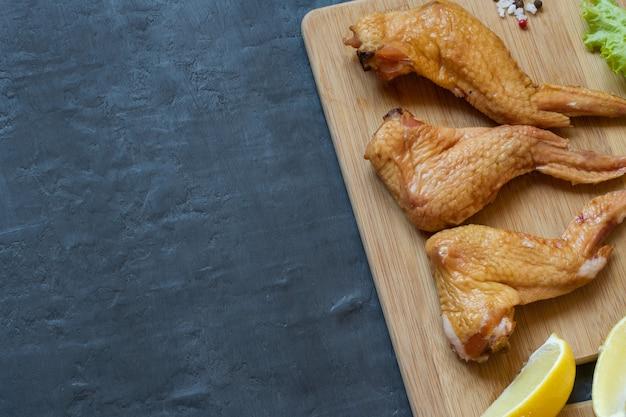 Geräucherte hühnerflügel auf einem hölzernen hackenden brett mit gemüse. dunkler hintergrund