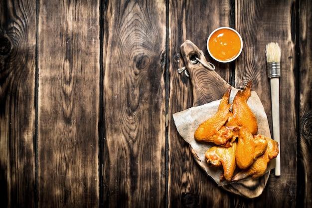 Geräucherte hühnerflügel mit sauce. auf einem holztisch.