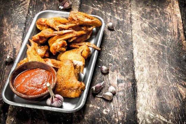 Geräucherte hühnerflügel mit soße auf holztisch.