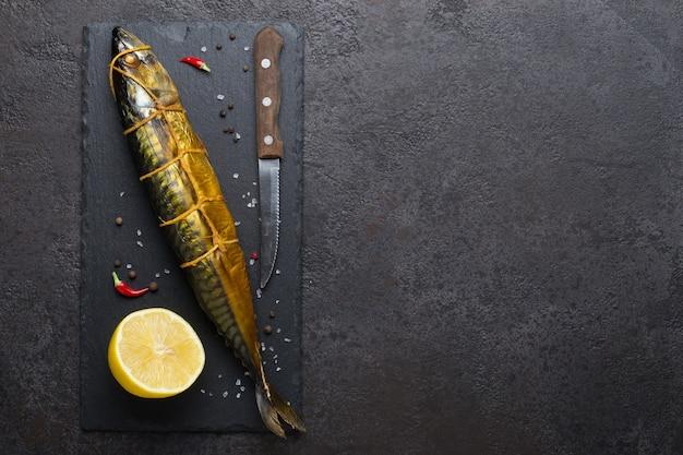 Geräucherte makrele, messer und zitrone auf schwarzem steinschneidebrett, kopierraum.
