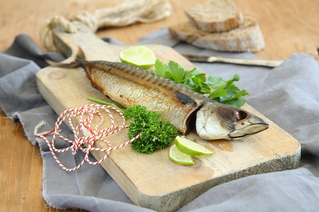 Geräucherte makrele mit kalk und petersilie auf hölzernem brett