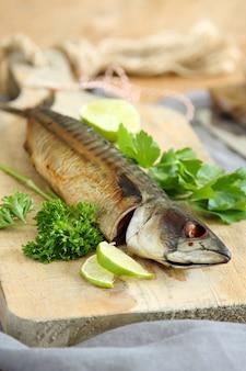 Geräucherte makrele mit kalk und petersilie auf holzbrett
