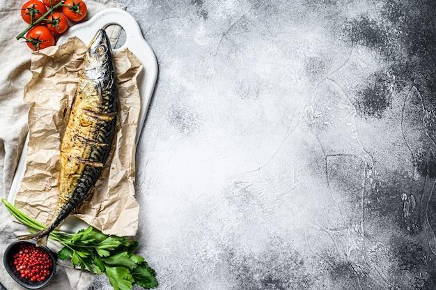 Geräucherte makrele mit petersilie und kirschtomaten. grauer hintergrund. draufsicht. platz für text