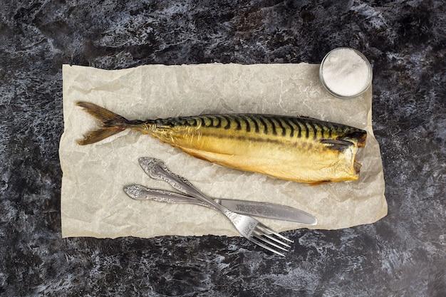 Geräucherte makrele ohne kopf mit gabelmesser auf backpapier