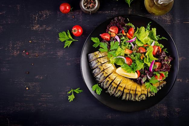 Geräucherte makrele und frischer salat auf dunklem hintergrund