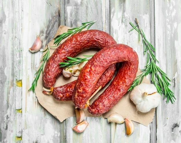Geräucherte salami mit knoblauch und kräutern. auf einem rustikalen.