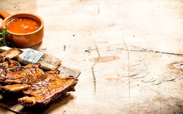 Geräucherte schweinerippchen mit scharfer soße und einem pinsel auf holztisch.