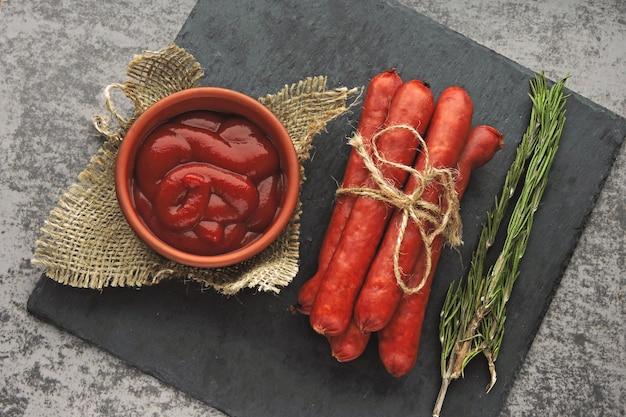 Geräucherte würstchen mit sauce und rosmarin. draufsicht.