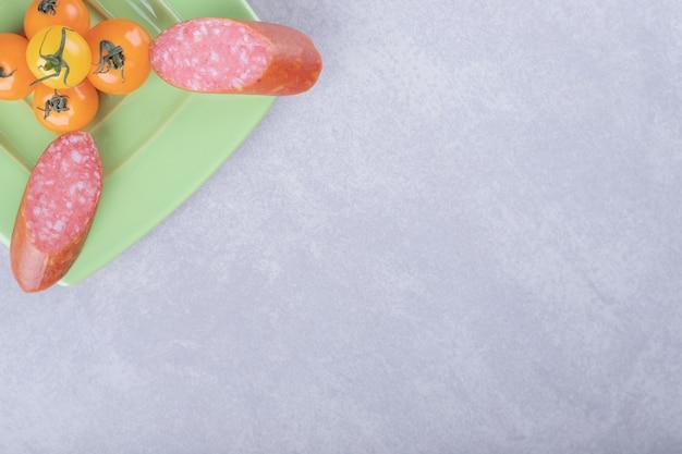 Geräucherte würste und kirschtomaten auf grüner platte.