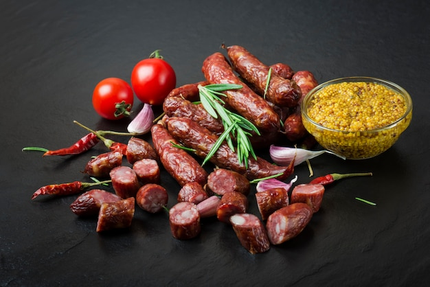 Geräucherte wurst mit rosmarin, pfeffer, tomaten und knoblauch auf schwarzem grund.
