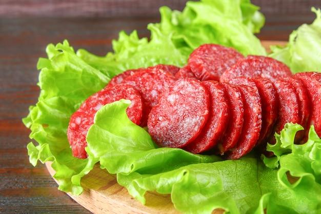 Geräucherte wurst, salami gehackt in scheiben auf einem salat auf einer hölzernen kreisschneidebrettbrauntabelle.