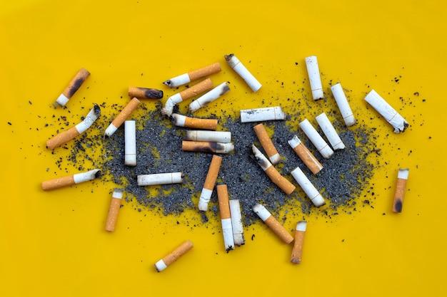 Geräucherte zigaretten auf gelber oberfläche