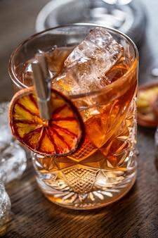 Geräucherter altmodischer cocktail mit eis in einem zierglas.