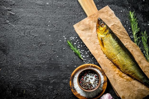 Geräucherter fisch auf papier mit gewürzen, rosmarin und knoblauch auf schwarzem rustikalem tisch.