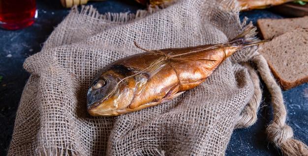 Geräucherter ganzer trockener fisch auf einem stück rustikalem gewebe