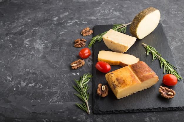 Geräucherter käse und verschiedene käsesorten mit rosmarin und tomaten auf schwarzem schieferbrett auf schwarzer betonoberfläche