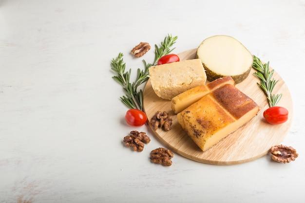 Geräucherter käse und verschiedene käsesorten mit rosmarin und tomaten