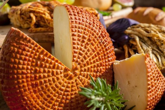 Geräucherter käsezopf, traditioneller polnischer geräucherter käse, chechil-käse auf dem hölzernen hintergrund.