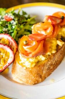 Geräucherter lachs mit zerbröckelten eiern auf toast