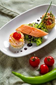 Geräucherter lachs, serviert mit kleinen portionen bulgur und salat