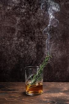 Geräucherter rosmarin in einem glas whisky oder bourbon