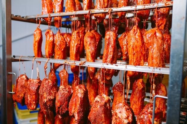 Geräucherter schinken im ofen. wurstproduktion in der fabrik.