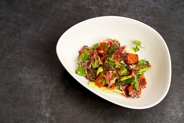 Geräuchertes entenfleisch mit gebackenem kürbis und salatblättern