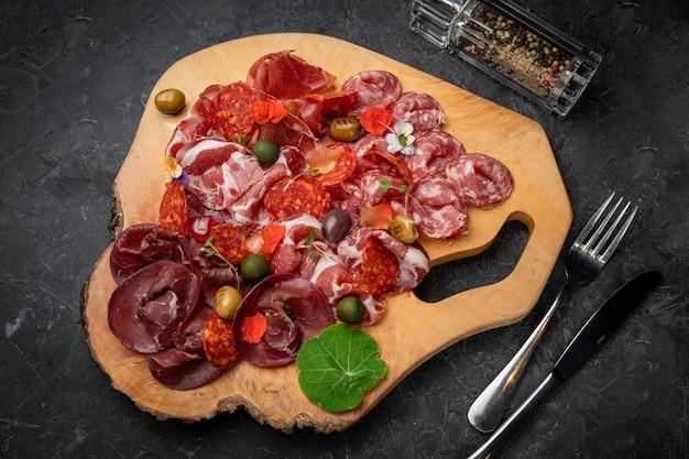 Geräuchertes fleisch, würstchen, parma, jamon auf einem holzbrett und einem dunklen betontisch.