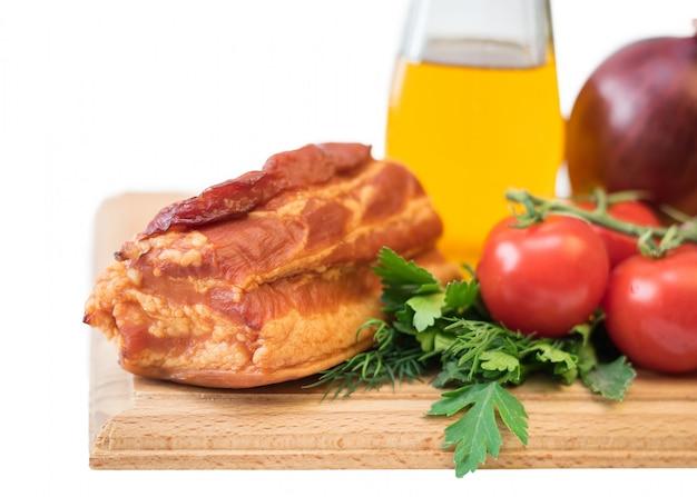 Geräuchertes schweinefleisch mit gewürzen auf einem hölzernen brett lokalisiert auf weiß.