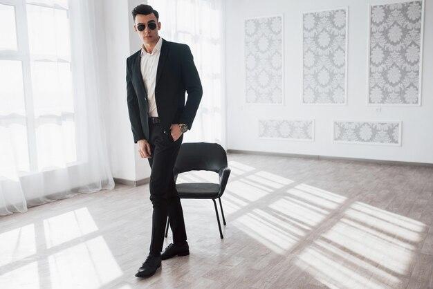 Geräumige fast leere halle mit schwarzem stuhl. porträt des jungen stilvollen mannes in der klassischen geschäftskleidung, die im weißen raum steht.