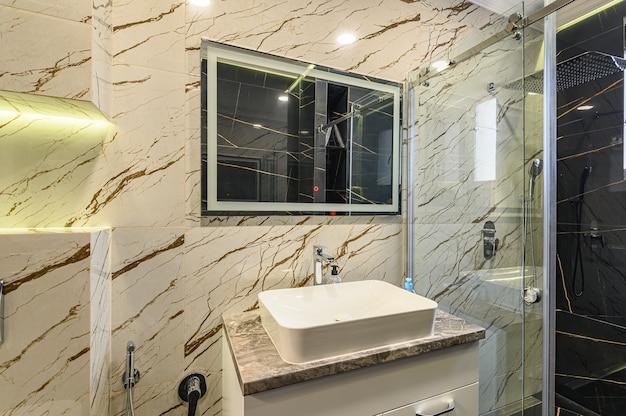 Geräumige luxus-badezimmerdetails in schwarz-weiß-tönen mit spiegel