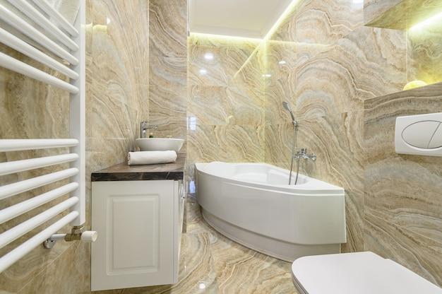 Geräumiges luxusbadezimmer mit weißem bad und beigen marmorfliesen