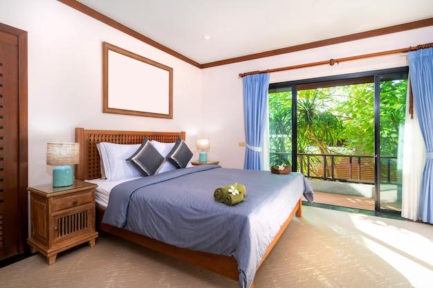 Geräumiges schlafzimmer mit blauem bettlaken und holzgarderobe