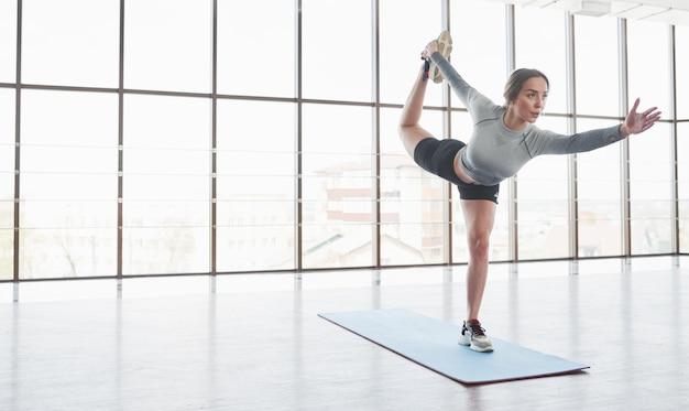 Geräumiges zimmer. sportliche junge frau haben fitness-tag im fitnessstudio zur morgenzeit