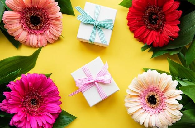 Gerbera blumen und geschenkboxen auf gelb. draufsicht