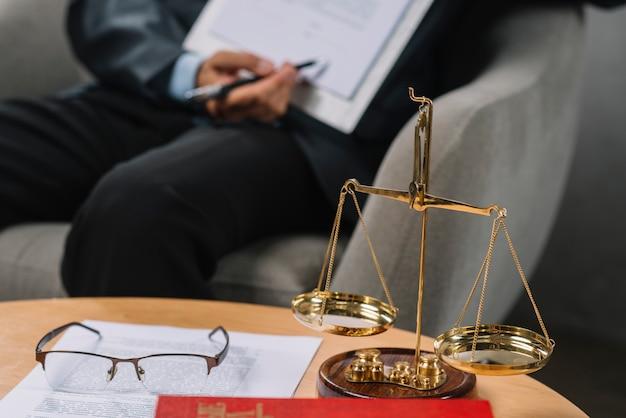 Gerechtigkeit der goldenen skala vor dem rechtsanwalt, der auf vertrag im gerichtssaal zeigt