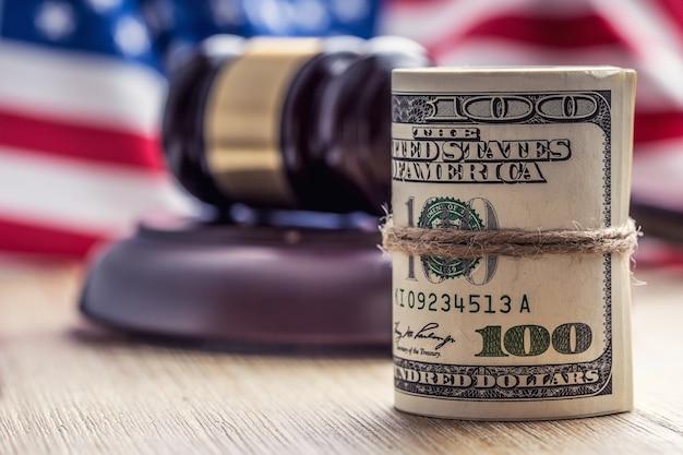 Gerechtigkeit dollar-banknoten und usa-flagge im hintergrund gerichtshammer und gerollte banknoten