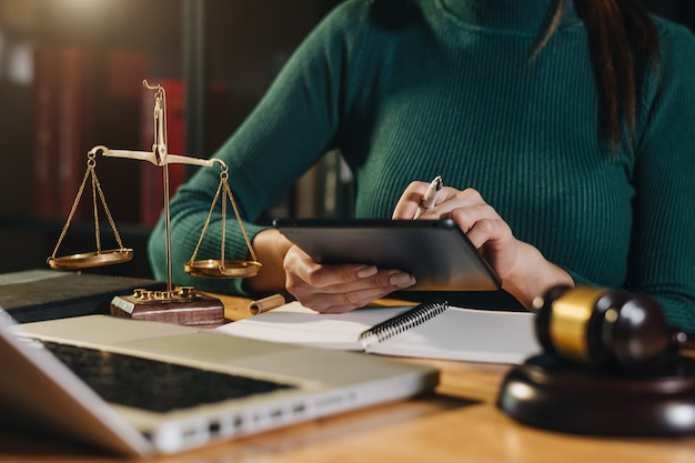 Gerechtigkeits- und rechtskonzept. männlicher richter in einem gerichtssaal, der mit smartphone und laptop und digitalem tablet-computer auf holztisch im morgenlicht arbeitet