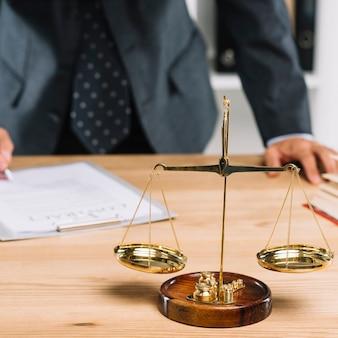 Gerechtigkeitsskala hinter dem rechtsanwalt, der das dokument auf schreibtisch unterzeichnet