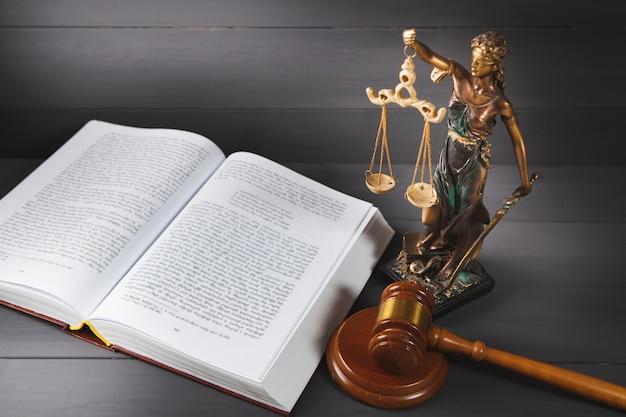 Gerechtigkeitsstatue, buch und hammer auf holztisch