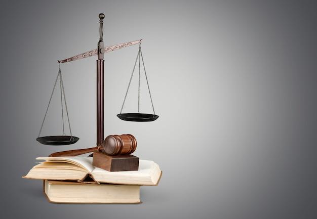 Gerechtigkeitswaagen und bücher und holzhammer auf dem tisch. gerechtigkeitskonzept